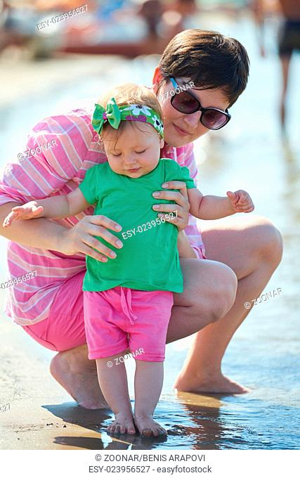 mom and baby on beach have fun