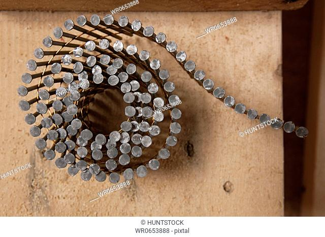 Coil of nails on a board