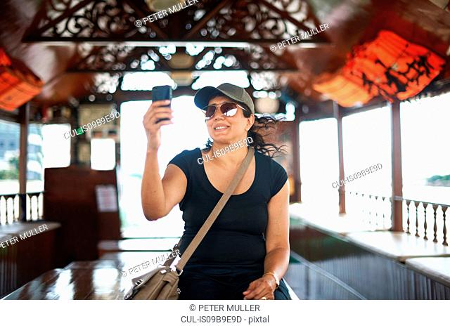 Woman taking selfie with smartphone smiling, Bangkok, Krung Thep, Thailand, Asia