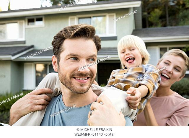 Happy parents with son in front of their home