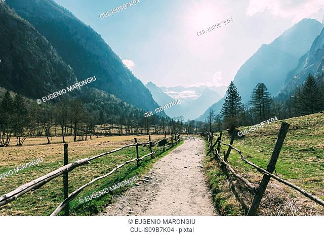 Landscape with valley dirt track and mountains, Mello, Lombardy, Italy