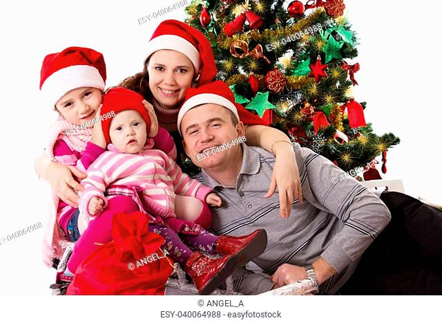Happy family with two little daughters under Chritmas tree over white