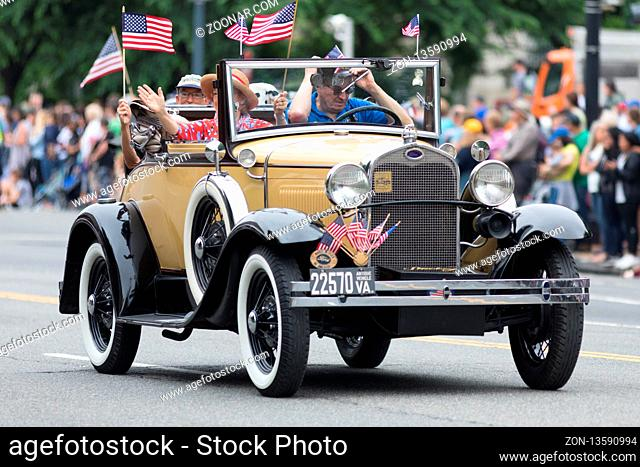 Washington, D.C., USA - May 28, 2018: The National Memorial Day Parade, Pople Waving american flags riding on Ford Model A classic cars, down contitution avenue