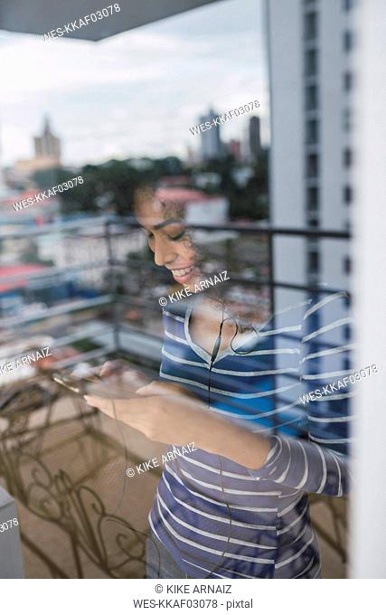 Smiling young woman behind windowpane using smartphone and earphones