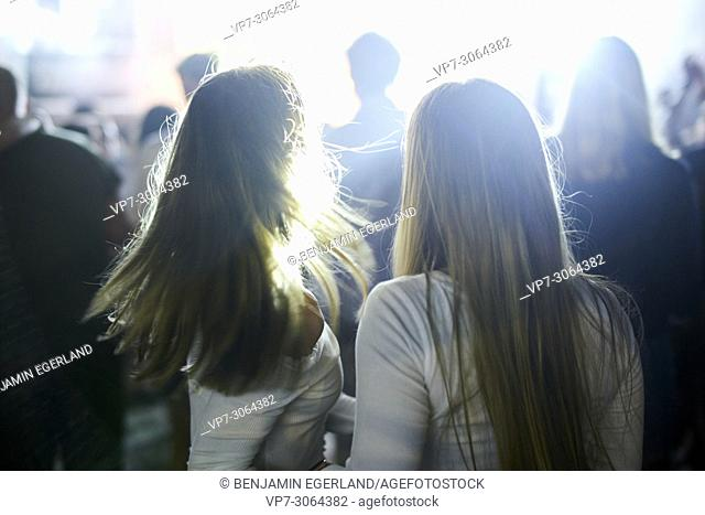 back of two women at music concert, shaking hair