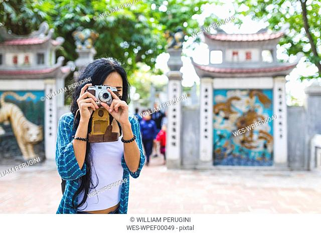 Vietnam, Hanoi, young woman taking a picture with old-fashioned camera