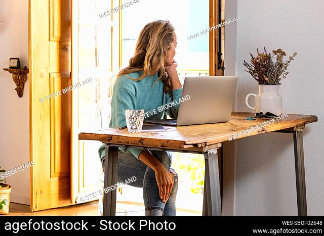 Thoughtful female freelancer looking away while sitting at home office