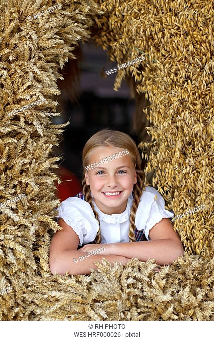 Germany, Luneburger Heide, portrait of smiling blond girl in harvest crown
