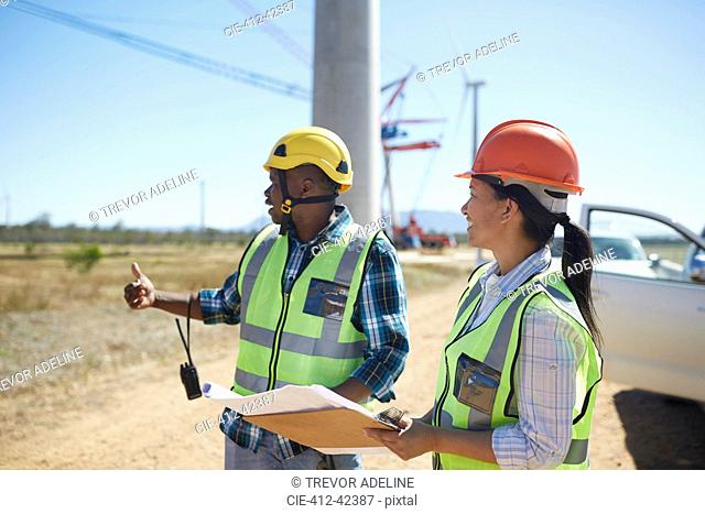 Engineers with blueprints talking at sunny power plant
