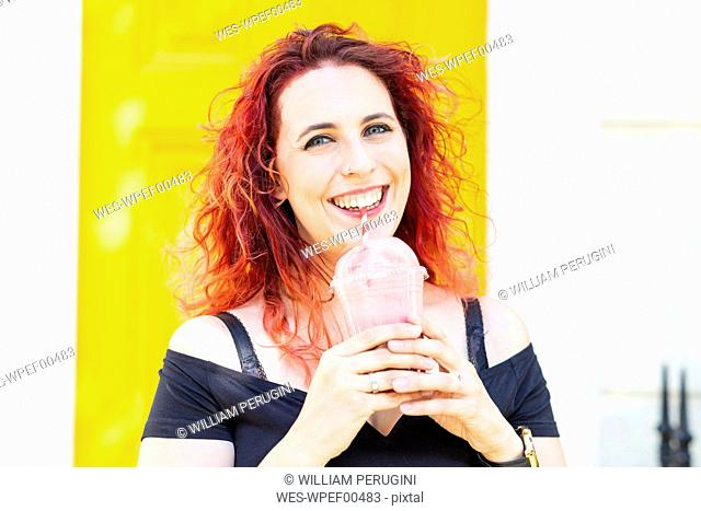 Portrait of laughing woman drinking smoothie