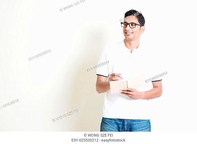 Portrait of Indian guy taking note on book, looking at side and smiling. Asian man standing on plain background with shadow and copy space