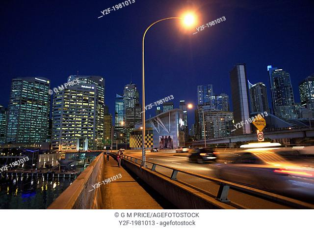 two people walking by Western Distributor Freeway at night, against illuminated Sydney skyline