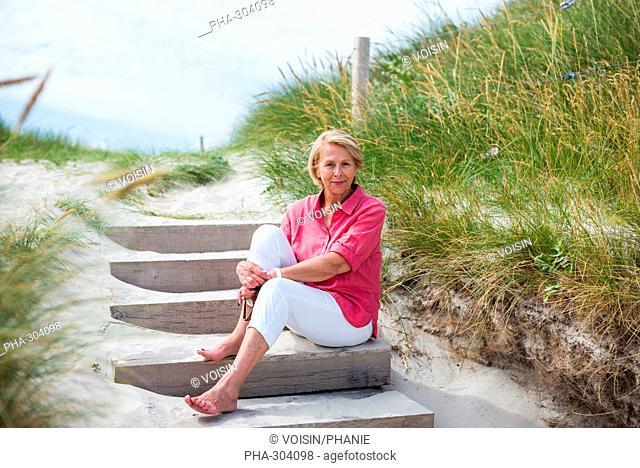 Senior sitting on the sand