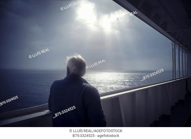 A man from behind on the deck of a boat looking at the sea. Mediterranean Sea
