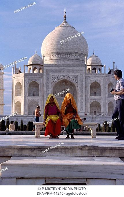 women sitting at Taj mahal Seventh Wonder of The World ; Agra ; Uttar Pradesh ; India