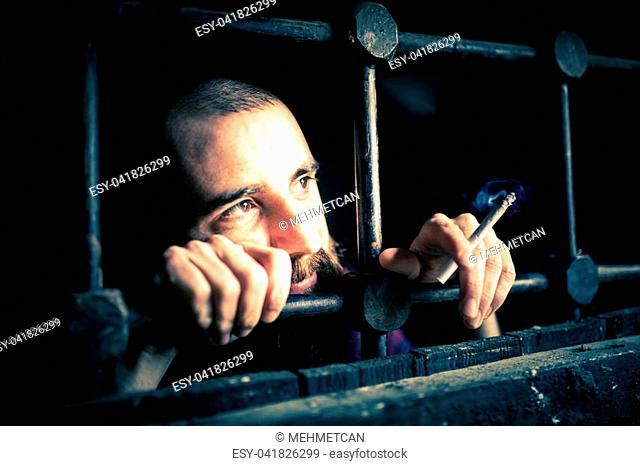 a helpless prisoner between the bars