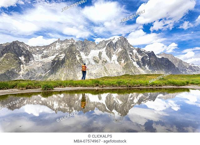 A girl is watching the Grandes Jorasses and the Mont Blanc Massif from the Mont de la Saxe during the Mont Blanc hiking tours (Ferret Valley, Courmayeur