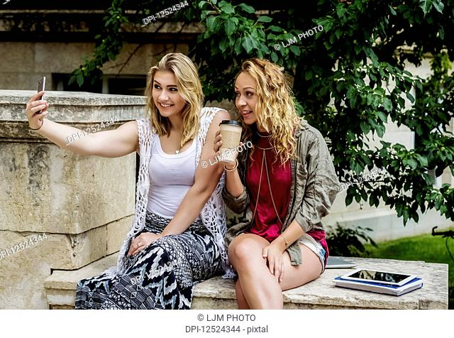 Two female university students sitting together on the campus taking a self-portrait with their smart phone; Edmonton, Alberta, Canada