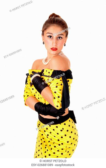 A beautiful young woman standing in a yellow dress and black cloves.isolated for white background.