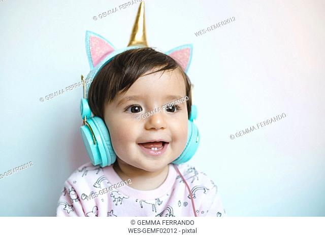 Portrait of smiling baby girl with unicorn headphones listening music