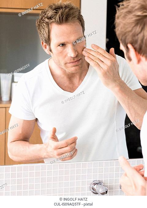 Mid adult man looking in bathroom mirror applying face cream