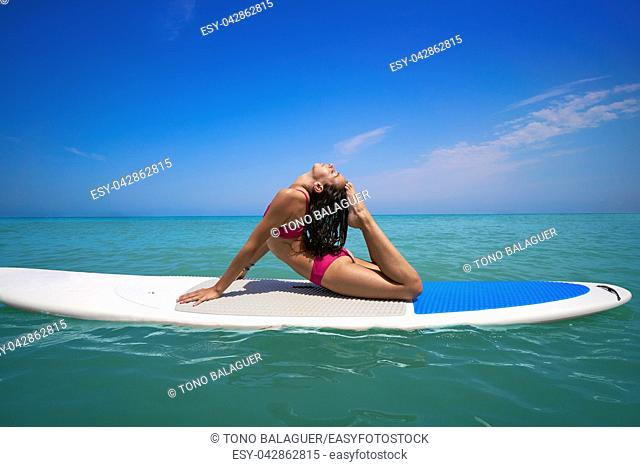 Girl gymnastics on paddle surf board SUP in summer yoga