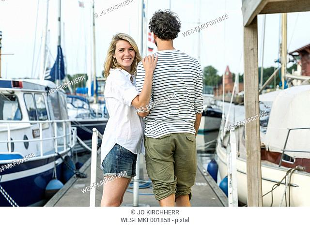Germany, Luebeck, smiling couple at marina