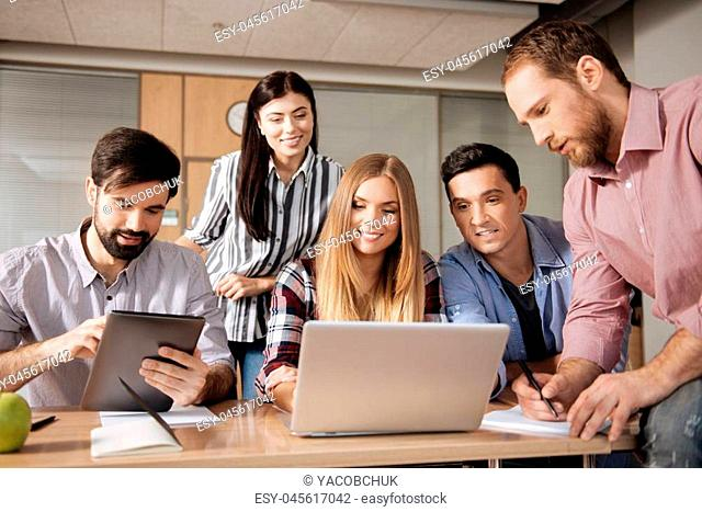 Well done. Attractive blonde keeping smile on face sitting in the middle of her friends while working with computer
