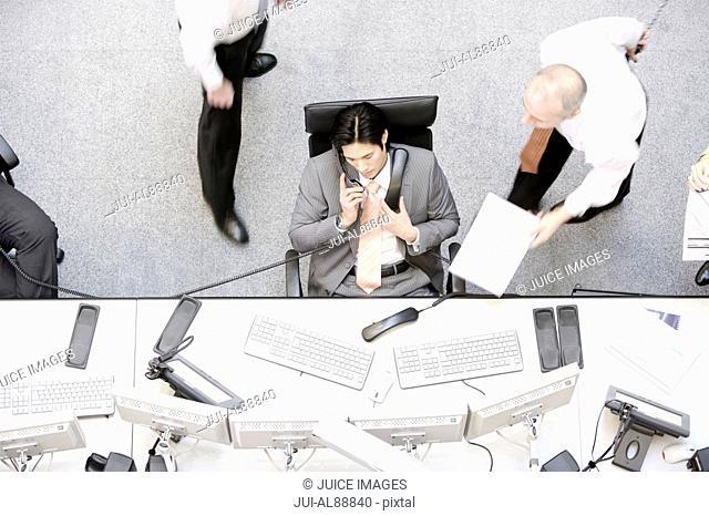 Businessman using multiple telephones