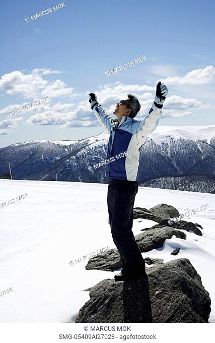 Man standing on snow covered mountain with arms up