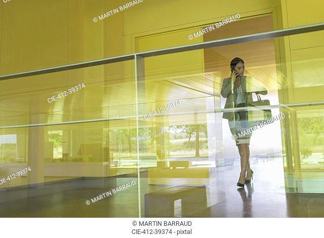 Businesswoman talking on cell phone and checking wristwatch in modern office