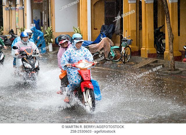 Scooter motorbike riders in Hoi An ride through the flooded streets, Vietnam