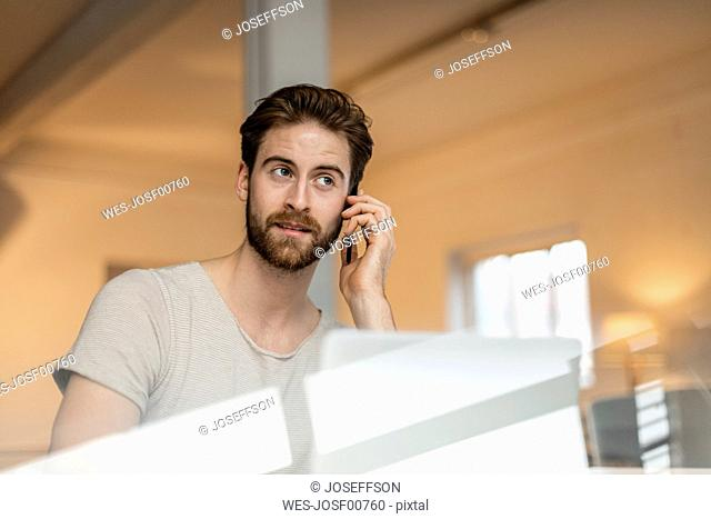 Portrait of young man on the phone in a loft