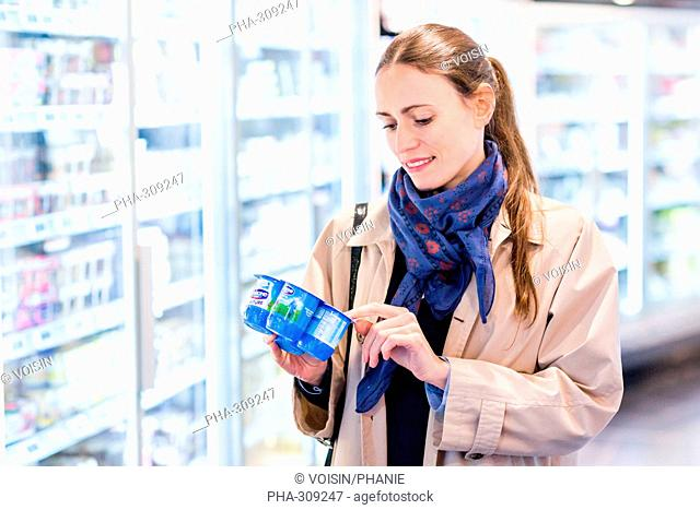 Woman shopping for dairy products in organic supermarket