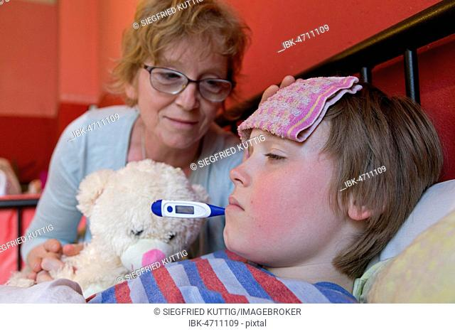 Mother comforts sick son in bed, symbol picture, cold, care, parents, childhood, Germany