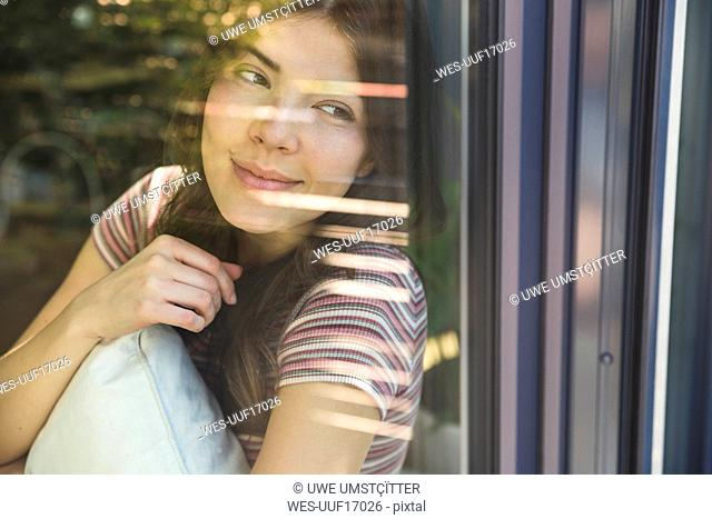 Portrait of smiling young woman behind windowpane
