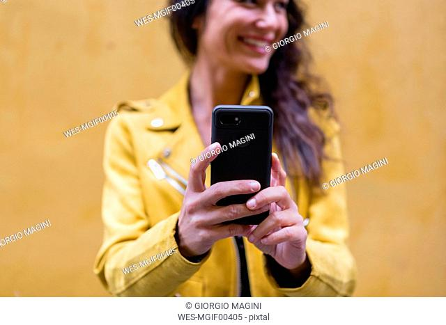 POrtrait of young woman wearing yellow leather jacket and taking a selfie, yellow wall in the background
