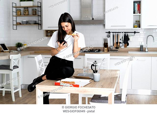 Young woman with cell phone eating pizza in kitchen at home
