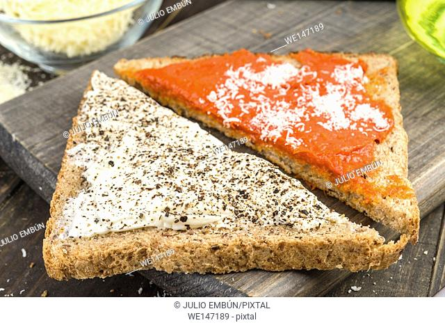 triangles of wholemeal bread spread with cream cheese and spicy sausage on wood