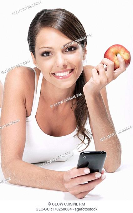 Woman holding a red apple and using a mobile phone