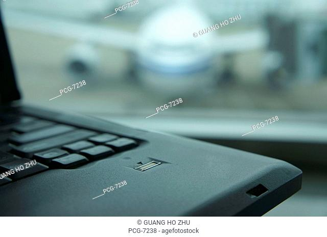A computer laptop on a surface, in front of a window. Airport apron and aircraft seen through the window