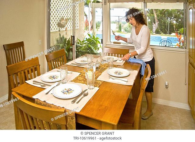 A 50-year-old woman sets a dining table for luncheon guests in Mission Viejo, California. Note swimming pool in outdoor background