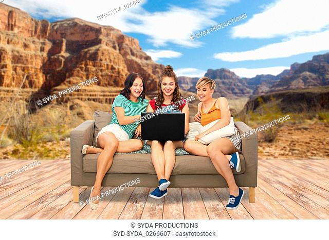 friends with laptop computer over grand canyon