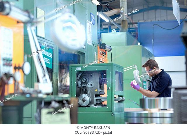 Engineer inspecting pressed metal part in metal pressing factory