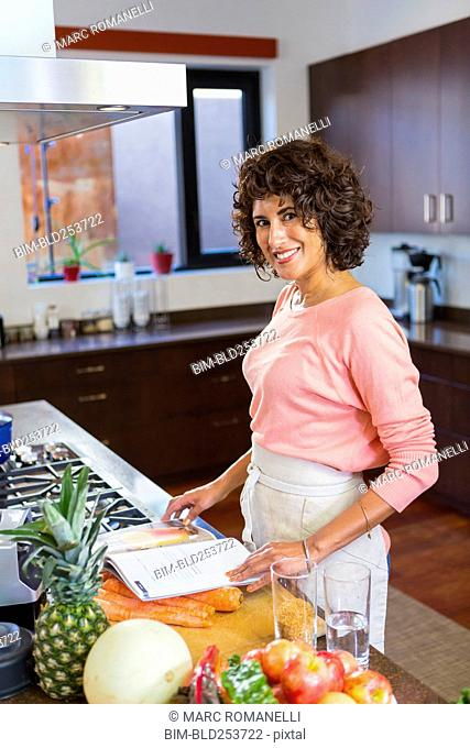 Hispanic woman reading cookbook in domestic kitchen
