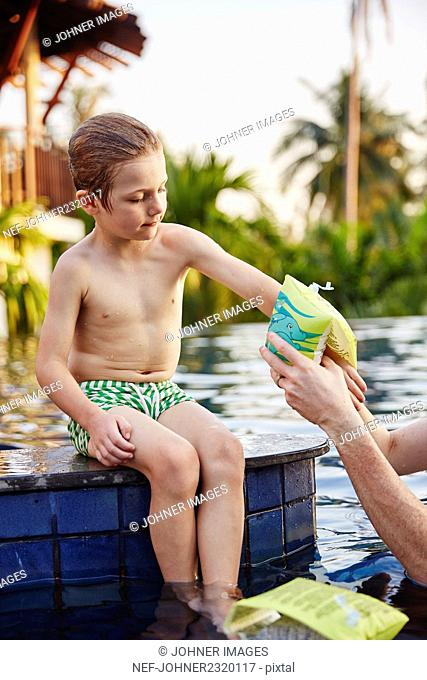 Father helping son with arm bands