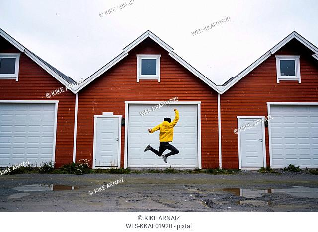 Norway, man jumping in front of row of huts