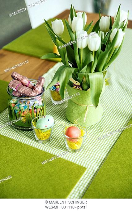 Easter table decoration with eggs, candy and tulips