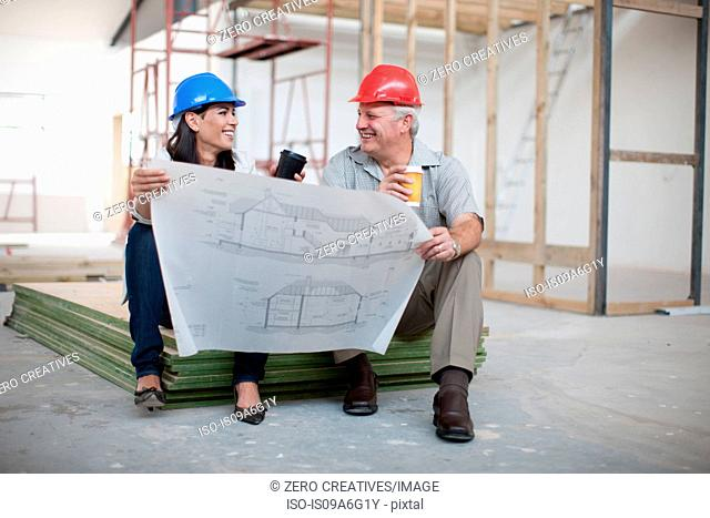 Male and female construction workers sitting down holding coffee and a blueprint