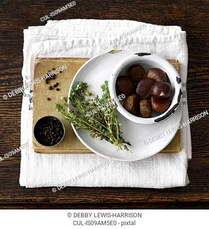 Chestnuts, plate, thyme, book, black pepper, kitchen towel